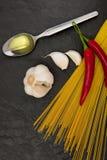 Ingredienti per l'olio di aglio e degli spaghetti sul fondo nero della pietra dell'ardesia Immagine Stock Libera da Diritti
