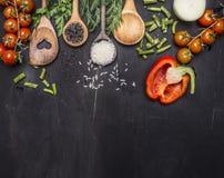 Ingredienti per la cottura dei cucchiai di legno dell'alimento vegetariano, pomodori ciliegia, aneto, prezzemolo, confine del pep Immagini Stock