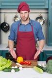 Ingredienti per la cottura dei piatti Punto dell'uomo alle verdure sulla tavola Cucini nel cappello e nel grembiule del cuoco uni Fotografie Stock Libere da Diritti