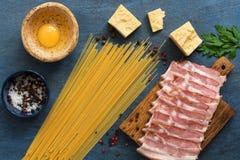 Ingredienti per la cottura del carbonara su un fondo blu, spaghetti, prosciutto, uovo, formaggio, spezie della pasta Vista superi immagini stock libere da diritti