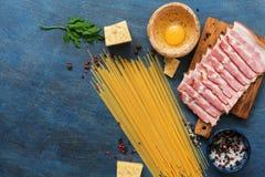 Ingredienti per la cottura del carbonara su un fondo blu, spaghetti, prosciutto, uovo, formaggio, spezie della pasta Vista superi fotografia stock libera da diritti