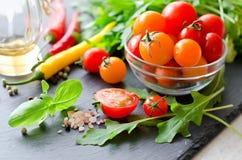 Ingredienti per la cottura dell'insalata con i pomodori ciliegia, erbe, peperoncino rosso immagini stock