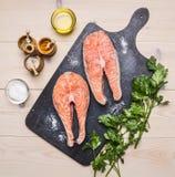 Ingredienti per la cottura della bistecca di color salmone cruda con le erbe, il prezzemolo, l'olio d'oliva ed il sale su buio d' Fotografia Stock