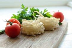 Ingredienti per la cottura della pasta italiana - spaghetti, pomodori, basilico ed aglio Immagine Stock