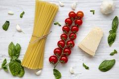 Ingredienti per la cottura della pasta su una tavola di legno bianca Disposizione piana Fotografie Stock Libere da Diritti