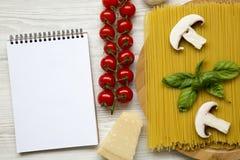 Ingredienti per la cottura pasta e del taccuino su un fondo di legno bianco Vista superiore Disposizione piana Immagini Stock