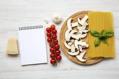 Ingredienti per la cottura pasta e del taccuino su un fondo di legno bianco Vista superiore Disposizione piana Fotografia Stock Libera da Diritti