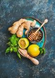 Ingredienti per la fabbricazione della bevanda calda naturale in piatto blu luminoso immagini stock