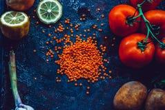 Ingredienti per la minestra di lenticchia turca casalinga con le lenticchie, pomodori, patata, erbe su un fondo scuro Fotografia Stock