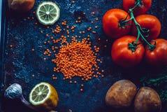 Ingredienti per la minestra di lenticchia turca casalinga con le lenticchie, pomodori, patata, erbe su un fondo scuro Fotografie Stock