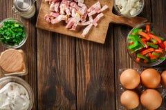 Ingredienti per la preparazione dell'omelette con bacon e le verdure Immagini Stock