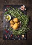 Ingredienti per le patate dei rosmarini con le spezie, l'aglio e l'olio Fotografia Stock