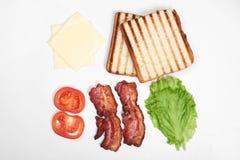 Ingredienti per produrre panino ortaggi freschi, pomodori, pane, becon, formaggio Isolato su fondo bianco, cima fotografia stock libera da diritti