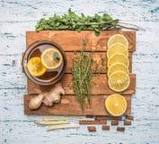 Ingredienti per produrre tè fragrante su un vassoio, su uno zenzero, su un limone, su una menta e su una cannella di legno su un  fotografia stock libera da diritti