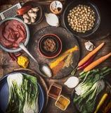 Ingredienti sani del vegetariano o del vegano: ceci, erbe, spezie, zenzero e cavolo cinese su fondo rustico immagini stock