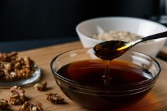 Ingredienti sani della prima colazione: miele, noci, farina d'avena immagine stock