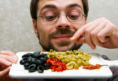 Ingredients. Closeup male holding plate with cutted green and black olives and hot pepper Royalty Free Stock Image