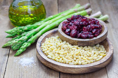 Ingredients for an appetizer with asparagus, pine nuts and cranberries Royalty Free Stock Image