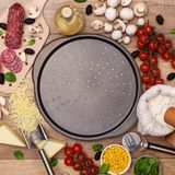 Ingredients around a pan ready to make a fresh homemade pizza. Ingredients around baking pan ready to make a fresh homemade pizza - with large copy space in the stock photography