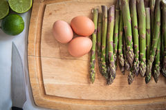 Ingredients for an asparagus salad. On a chopping board: asparagi, eggs, lime Royalty Free Stock Photography