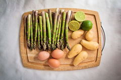 Ingredients for an asparagus salad. On a chopping board: asparagi, eggs, potatoes, lime Royalty Free Stock Photography