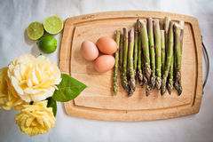 Ingredients for an asparagus salad with roses. Ingredients for an asparagus salad on a chopping board: asparagi, eggs, lime and yellow roses Stock Photos