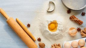 Ingredients for baking cake and accessories with copy space: rolling pin, eggs, ginger, anise stars, cinnamon and bakewares. Baking background. Top view Stock Photography