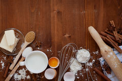 Ingredients for baking dough including flour, eggs, milk, butter, sugar, cinnamon, anise star, whisk and rolling pin on wooden rus. Tic background, empty space Royalty Free Stock Image