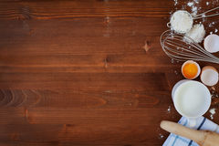 Ingredients for baking dough including flour, eggs, milk, whisk and rolling pin on wooden rustic background. Empty space for text, top view Royalty Free Stock Photography