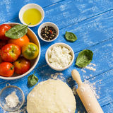 Ingredients for baking . dough, tomatoes, feta cheese - the ingredients to make a pie with tomatoes and cheese Royalty Free Stock Images