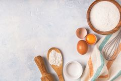 Ingredients for baking - flour, wooden spoon, eggs. Ingredients for baking - flour, wooden spoon, rolling pin, eggs. Top view, copy space royalty free stock image