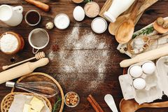 Ingredients for baking and kitchen utensils. Flour, eggs, sugar. On wooden background royalty free stock images