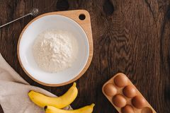 The ingredients for the banana cake flour egg on wooden table. The ingredients for the banana cake flour egg on wooden table Stock Photos