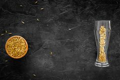 Ingredients for beer. Malting barley in beer glass on black background top view copyspace. Ingredients for beer. Malting barley in beer glass on black background Royalty Free Stock Photos