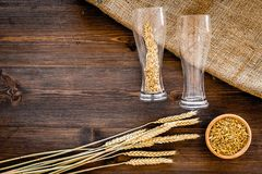 Ingredients for beer. Malting barley in beer glass on wooden background top view copyspace. Ingredients for beer. Malting barley in beer glass on wooden Royalty Free Stock Photography