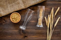 Ingredients for beer. Malting barley in beer glass on wooden background top view.  Stock Photos