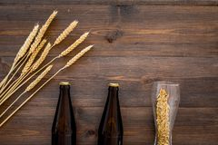 Ingredients for beer. Malting barley near beer bottle and glass on wooden background top view copyspace. Ingredients for beer. Malting barley near beer bottle Royalty Free Stock Photography