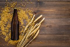 Ingredients for beer. Malting barley near beer bottle and glass on wooden background top view copyspace. Ingredients for beer. Malting barley near beer bottle Stock Photos