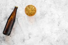 Ingredients for beer. Malting barley near beer glasses and bottle on grey background top view copyspace. Ingredients for beer. Malting barley near beer glasses Stock Images