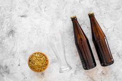 Ingredients for beer. Malting barley near beer glasses and bottle on grey background top view copyspace. Ingredients for beer. Malting barley near beer glasses Royalty Free Stock Photography