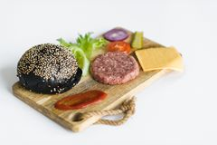 Ingredients for the black Burger on wooden cutting Board. stock image