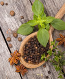 Ingredients. Black peppercorns on a wooden spoon surrounded by other spices and herbs including star anise, basil and thyme stock photos