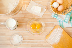 Ingredients for bread baking. Ingridients for bread baking on light wooden background. Cutting board, eggs, salt, flour, raw eggs, milk, butter, towel, sieve Royalty Free Stock Photos
