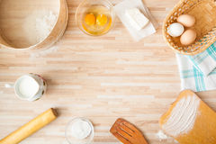 Ingredients for bread baking. On light wooden background  with copyspace. Cutting board, eggs, salt, flour, raw eggs, milk, rolling pin, butter, towel, sieve Stock Photography