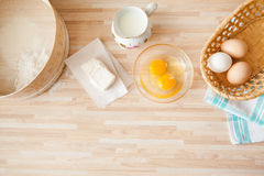 Ingredients for bread baking. On light wooden background  with copyspace. Eggs in braided bucket, flour, raw eggs, milk, butter, towel, sieve. Cusine background Royalty Free Stock Photography