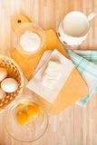 Ingredients for bread baking. On light wooden table. Butter and salt on cutting board and towel, eggs, raw eggs, milk Stock Photo