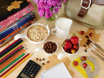 Ingredients for breakfast surrounded by school supplies Royalty Free Stock Images