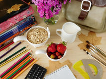 Ingredients for breakfast surrounded by school supplies Stock Images