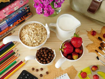 Ingredients for breakfast surrounded by school supplies Royalty Free Stock Photo