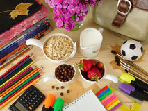 Ingredients for breakfast surrounded by school supplies Royalty Free Stock Photos